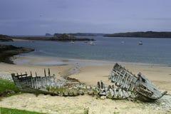 El esqueleto de madera de una nave arruinó en una playa pedregosa contra un cielo nublado azul con las islas detrás Escocia del n foto de archivo