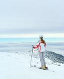 El esquiador admira en hermosa vista del top de la montaña Fotografía de archivo libre de regalías