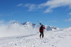 El esquiador con los esquís sube al top de la montaña Imágenes de archivo libres de regalías