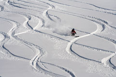 El esquiador de la montaña va abajo en nieve del polvo Imagenes de archivo