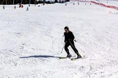 El esquiador desciende de la montaña en el funcionamiento de esquí Fotos de archivo libres de regalías