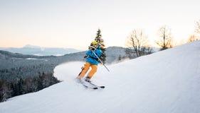 El esquiador en polvo de la nieve produce el frenado en la cuesta de la montaña Imagen de archivo libre de regalías