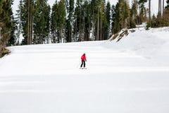 El esquiador está esquiando abajo de la cuesta en el bosque Imagenes de archivo