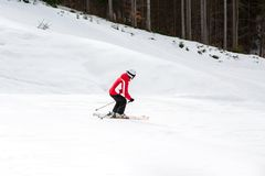El esquiador está esquiando abajo de la cuesta en el bosque Imagen de archivo