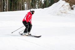 El esquiador está esquiando abajo de la cuesta en el bosque Imágenes de archivo libres de regalías