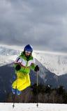 El esquiador joven salta con los polos de esquí en montañas del invierno del sol Fotografía de archivo libre de regalías