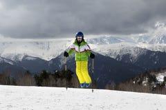 El esquiador joven salta con los polos de esquí en montañas del sol y gris nublado Fotografía de archivo