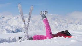 El esquiador lanza para arriba nieve en el aire, aumenta su pierna y cae en la nieve almacen de video