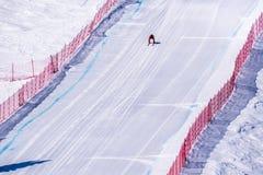 El esquiador que compite con abajo de la cuesta escarpada del esquí de la velocidad en el desafío de la velocidad y FIS apresuran Foto de archivo
