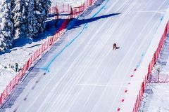 El esquiador que compite con abajo de la cuesta escarpada del esquí de la velocidad en el desafío de la velocidad y FIS apresuran Imagenes de archivo