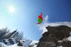El esquiador que salta contra el cielo azul de la roca Imágenes de archivo libres de regalías