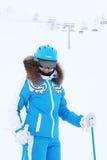 El esquiador sonriente de la mujer mira la cámara Imágenes de archivo libres de regalías