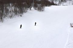 El esquiador y el snowboarder en el esquí se inclinan en el día de invierno gris Fotografía de archivo libre de regalías