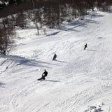 El esquiador y los snowboarders en el esquí se inclinan en el día de invierno del sol Fotos de archivo libres de regalías