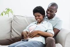 El estómago conmovedor de la mujer embarazada del hombre en el sofá Fotografía de archivo libre de regalías