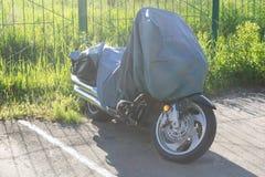 El estacionamiento es una motocicleta, cubierta con un abrigo de la lona Imagenes de archivo