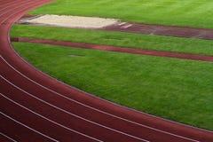 El estadio de los deportes con las pistas de raza y el salto de longitud marcan con hoyos Imagenes de archivo