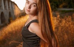 El estado de ánimo de la calma de la mujer joven n con el pelo rubio largo hecho excursionismo por el foco selectivo del sol ento Foto de archivo