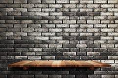El estante de madera vacío del tablero en el fondo negro de la pared de ladrillo, imita encima de las FO imagen de archivo libre de regalías
