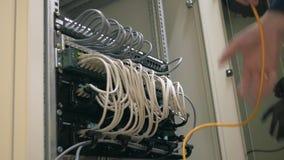 El estante y el enchufe abiertos del servidor del ingeniero de las TIC hacia fuera telegrafían metrajes