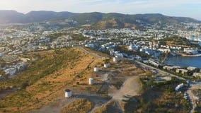 El estar en órbita aéreo alrededor de los molinoes de viento en la colina Ciudad de vacaciones Bodrum con las casas blancas en el almacen de video
