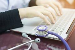 El estetoscopio en el escritorio y los woman's borrosos del doctor dan el teclado que mecanografía del cuaderno para trabajar e Fotos de archivo libres de regalías