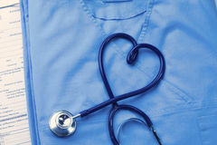 El estetoscopio médico torcido en la forma del corazón que miente en doctor paciente de la lista y del azul del historial médico  Imágenes de archivo libres de regalías