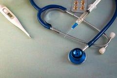 El estetoscopio texturizó el fondo, píldoras, termómetro, jeringuilla Imagen de archivo libre de regalías