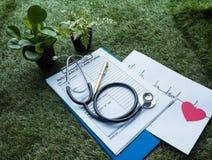 El estetoscopio y el corazón rojo con el cardiograma del ritmo cardíaco que dibuja en el papel, con la forma de demanda de seguro imagen de archivo