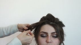 El estilista asperja el pelo con el modelo metrajes