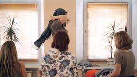 El estilista en el entrenamiento muestra cómo atar la bufanda de moda en la cabeza almacen de video