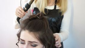 El estilista enrolla el pelo con un hierro que se encrespa almacen de metraje de vídeo
