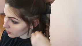 El estilista envuelve el pelo del modelo en un hierro que se encrespa metrajes