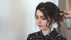 El estilista fija morenita de la muchacha del pelo metrajes