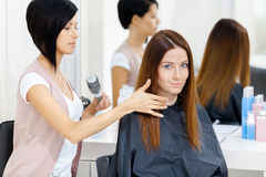 El estilista hace el estilo de pelo de la mujer en salón de la peluquería