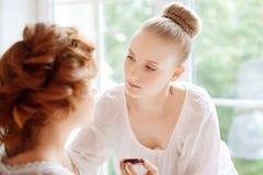 El estilista hace a la novia del maquillaje antes de la boda foto de archivo