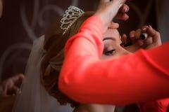 El estilista hace a la novia del maquillaje en el día de boda fotos de archivo libres de regalías
