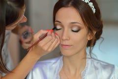 El estilista hace a la novia del maquillaje en el día de boda fotos de archivo