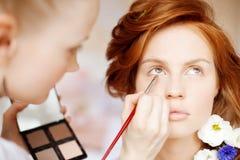 El estilista hace a la novia del maquillaje en el día de boda Imagen de archivo