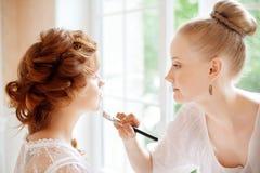 El estilista hace a la novia del maquillaje en el día de boda Foto de archivo