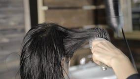 El estilista hace el pelo que diseña para el cliente femenino hermoso y el secador de pelo usado con el peine metrajes