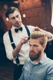 El estilista hermoso vestido con clase de la peluquería de caballeros está haciendo un h perfecto fotografía de archivo