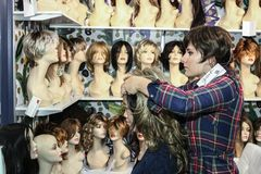 El estilista intenta la peluca en cliente Imagenes de archivo