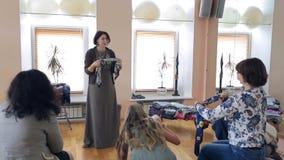 El estilista moreno explica a las mujeres cómo atar la bufanda de seda en oficina metrajes