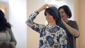 El estilista muestra en modelo cómo atar la bufanda en su cabeza metrajes