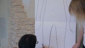 El estilista muestra estilos favorables por exhausto en el contorno de papel del cliente almacen de video