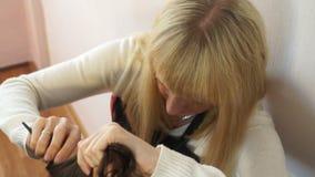 El estilista peina el pelo en el jefe del modelo almacen de metraje de vídeo