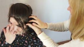 El estilista pone el pelo en el jefe del modelo almacen de video