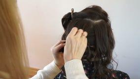 El estilista pone un filamento del pelo metrajes