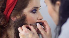 El estilista profesional crea un carácter escénico para la actriz joven almacen de video